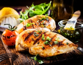 Marinated grilled healthy chicken breasts cooked on a summer BBQ and served with fresh herbs and lemon juice on a wooden board, close up view